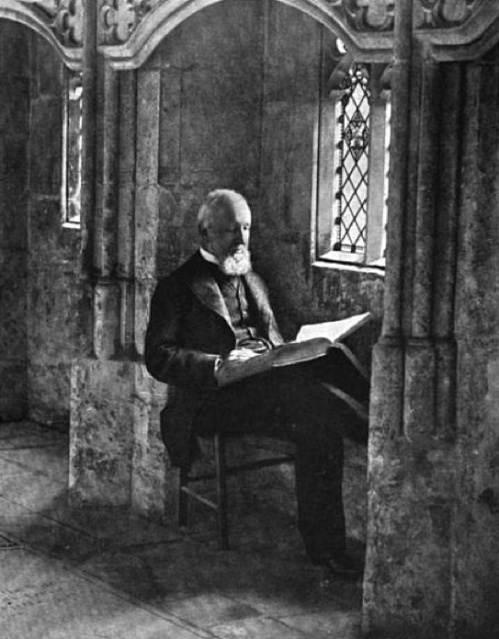 A gentleman enjoys a book in one of Gloucester's south cloister carrels.